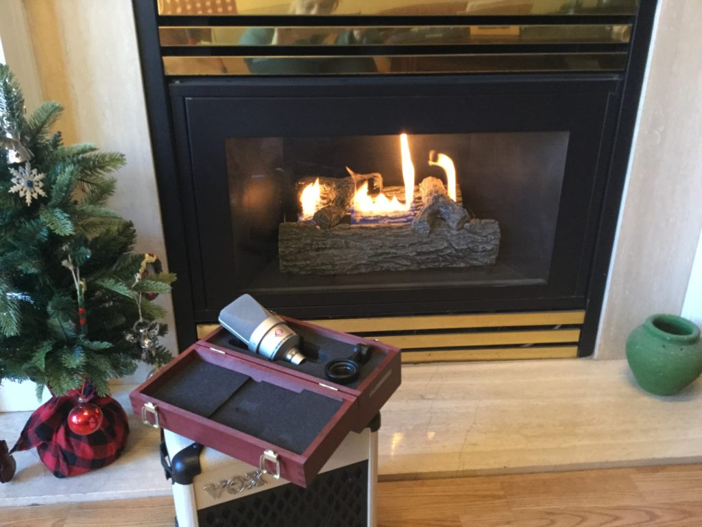 Microphone sitting in wooden case in front of a fire and a Christmas tree.